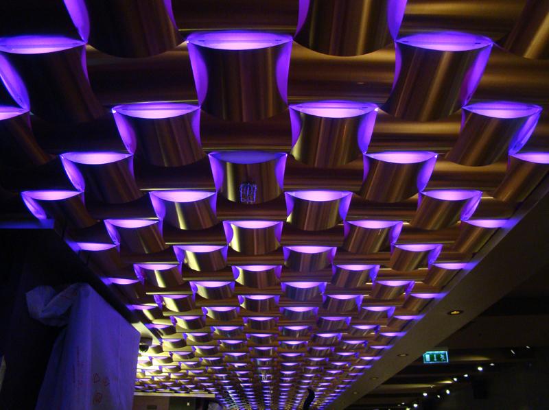 A szegmentált mennyezeti és oldalfal fémburkolat tetszőleges formájú és színű elemekből állítható össze és az adottságoktól és igényektől függő színű és technológiájú világítással kombinálható