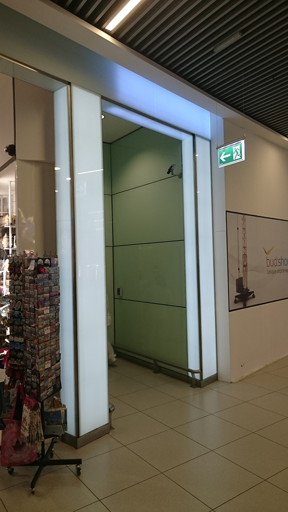 Üvegburkolat és világítástechnika kombinációja, sík és ívelt üvegburkolatok a SkyCourtban. A fénysávok közrefogják az üzletek portáljait.